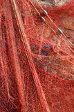 A red fishing net hanging on a wall Stock Image