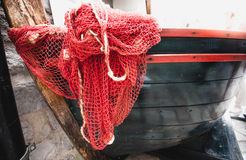 Red fishnet lying blue wooden rowboat Royalty Free Stock Photos