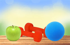 Red fitness dumbbells, blue ball and green apple on wooden table Stock Photos