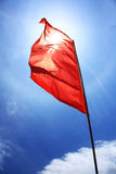 Red Flag. A red flag waving in the wind under the bright sun Stock Photo