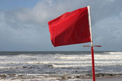 Red Flag. A red flag cautions swimmers, against the backdrop of an angry sea royalty free stock photo