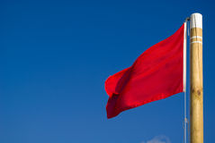 Red flag. Closeup in a beach.  is a sign of warning and means that it's not advisable to take a bath. Many uses and concepts Royalty Free Stock Images