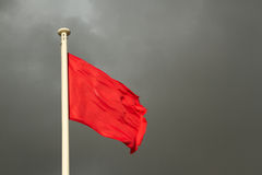Red flag. A white flag pole with a bright red flag against a grey cloudy sky Royalty Free Stock Image