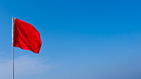 Red flag against blu skye Royalty Free Stock Photography