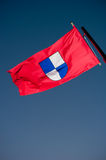 Red flag with amblem. Of Metkovic city in Croatia, Europe, flying on the wind Royalty Free Stock Image