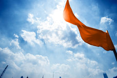 Red flag on a background of the dark blue sky with clouds. Royalty Free Stock Images