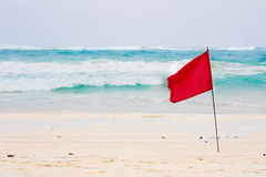Red flag on beach. During stormy day, no swimming stock image