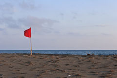Red flag on beach Royalty Free Stock Photography