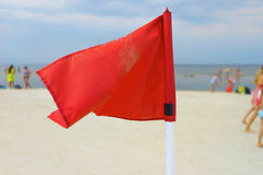 Red flag on the beach of the Baltic Sea. Latvia. Jurmala. 2015, summer. Red flag and blue sky on the sandy beach of the Baltic Sea on a sunny summer day Royalty Free Stock Images