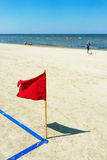 Red flag on the beach and a boy with a ball Royalty Free Stock Photos