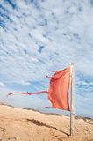 Red flag on the beach damaged by strong winds Royalty Free Stock Photos