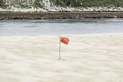 Red flag on the beach Royalty Free Stock Photography