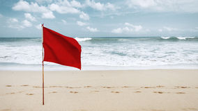 Red flag on the beach on the island of Bali Royalty Free Stock Photos