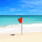 Red flag on the  beach on an island Royalty Free Stock Images