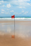 Red flag on beach with no swimming notes. Stock Photography