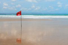 Red flag on beach with no swimming notes. Royalty Free Stock Images