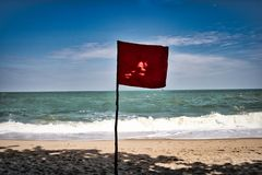 Red flag on a beach royalty free stock photography