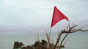 Red flag on a beach. Red flag on a rocky beach stock video footage