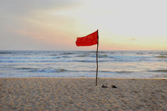 Red flag on the beach Royalty Free Stock Photos
