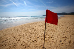 Red Flag, Beach Warning. A red flag erected on a beach, warning swimmers to stay off from the waves royalty free stock images