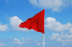 Red flag beach. Red flag waving on blue sky Stock Photography
