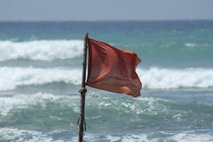 Red flag danger during a storm on the ocean Royalty Free Stock Images
