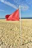 Red flag on flag pole blowing in wind. Red flag on flag pole blowing in breeze on seashore beach with blue sky background stock photos