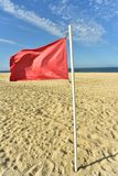 Red flag on flag pole blowing in wind. Red flag on flag pole blowing in breeze on seashore beach with blue sky background stock photography