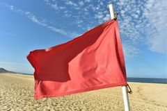 Red flag on flag pole blowing in wind. Red flag on flag pole blowing in breeze on seashore beach with blue sky background royalty free stock photos