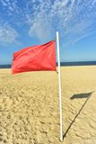 Red flag on flag pole blowing in wind. Red flag on flag pole blowing in breeze on seashore beach with blue sky background royalty free stock photography