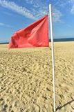 Red flag on flag pole blowing in wind. Red flag on flag pole blowing in breeze on seashore beach with blue sky background royalty free stock image