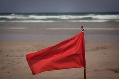 Red flag flap on the beach Stock Image