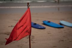 Red flag flap on the beach. Surfboards in background Royalty Free Stock Images