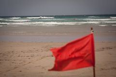 Red flag flap on the beach. Surfers in background Stock Photos