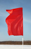 Red flag flutters in wind at background of sky Royalty Free Stock Image