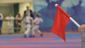 Red flag in front of teenager girls fighting at the karate tournament. Blurred stock video