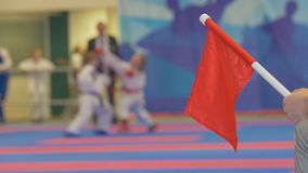 Red flag in front of teenager girls fighting at the karate tournament. Blurred Royalty Free Stock Photos