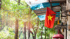 Red flag with a gold star of Vietnam fluttering on the street city Hanoi. On background green nature at sunny summer day / Vietnam royalty free stock photo