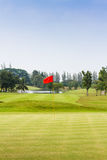 Red flag in golf course. Red flag at hole in golf course Royalty Free Stock Image