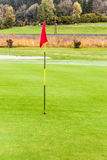 Red flag golf hole. A golf hole with a flag pole in a beautiful golf course Royalty Free Stock Image