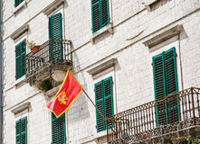 Red Flag and Green Shutters Stock Image