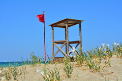 The red flag and the house of the lifeguard Royalty Free Stock Image