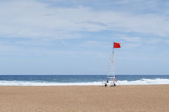 Red flag in the lifeguard station. In a lonely beach royalty free stock photography