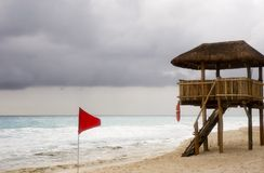 Red Flag and Lifeguard Station. A red flag indicating dangerous surf and an empty lifeguard station at the beach stock photos