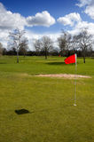 Red flag marking hole. Red flag marking the hole on the green putting surface of a manicured golf course in winter royalty free stock photo