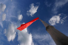 Red flag on mast. A red flag waving high on a mast, white clouds in the blue sky in the background Royalty Free Stock Images