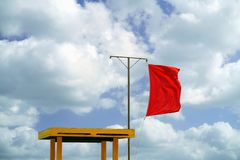 Red flag next to a lifeguard chair at the beach. Swimming in the sea is not allowed. royalty free stock photography