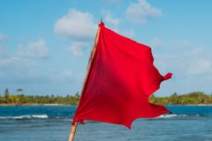 Red flag ocean background - beach warning symbol. Red flag windy weather at coastn stock image