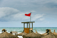 Red flag over the beach Stock Images