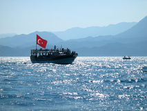 Red flag over turkish water. A tourist boat at sunset in Turkey royalty free stock photo